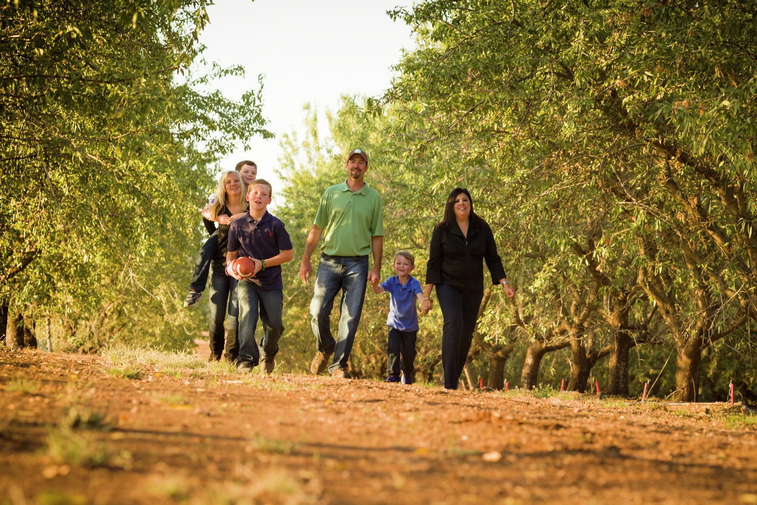 A family walking through an almond orchard.